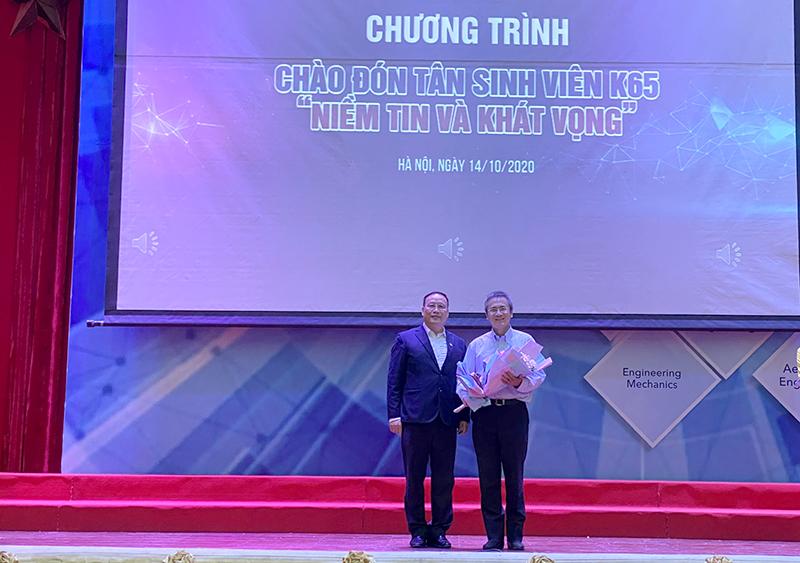GS. TSKH Nguyễn Đình Đức - Trưởng ban Đào tạo – Đại học Quốc gia Hà Nội (bên trái) tặng hoa TS. Phan Lê Bình - Chuyên gia JICA, Giảng viên Trường Đại học Việt Nhật (bên phải)